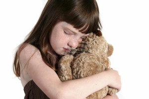 Seven year old girl hugging her teddy bear